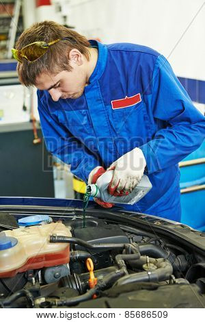 auto repairman mechanic worker changing antifreeze in car auto repair or maintenance shop service station