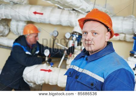 two repairman engineer of fire engineering system or heating system open the valve equipment in a boiler house
