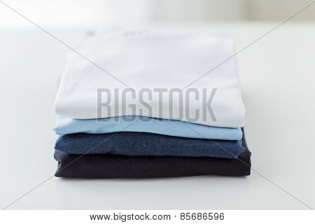 ironing, laundry, clothes, housekeeping and objects concept - close up of ironed and folded t-shirts on table at home