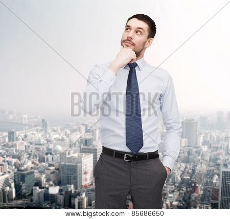 business and office concept - handsome businessman looking up