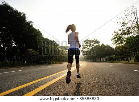 Runner athlete running at road. woman fitness sunrise jogging workout wellness concept.
