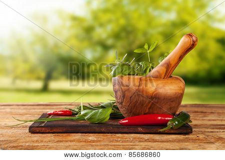 Various kind of spices on wooden table with mortar