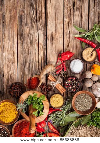 Various kind of spices on wooden table, shot from aerial view