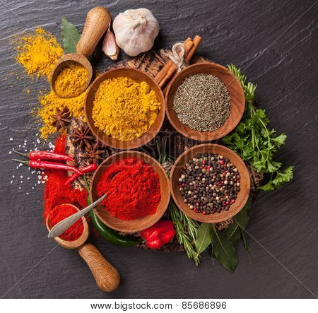 Various spices on black stone shot from aerial view