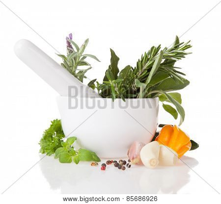 Various kind of fresh herbs in ceramic grinder. Isolated on white background