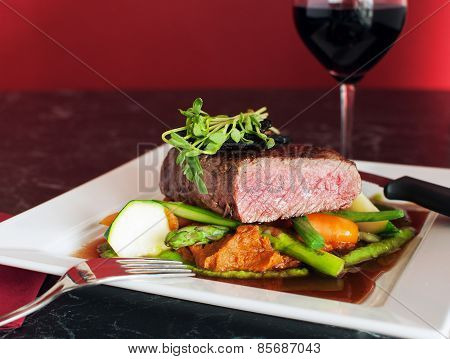Medium beef steak on bed of vegetables