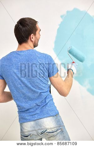 repair, building, people and renovation concept - man with roller painting wall in blue at home