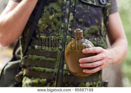 war, hiking, army and people concept - close up of young soldier or ranger with gun drinking from flask in forest