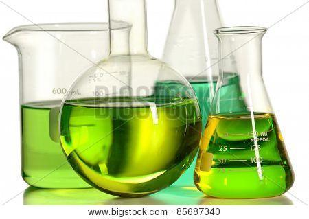 laboratory glassware with liquid over reflective table