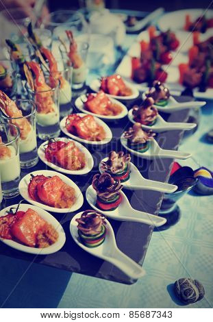 Spoons with seafood snacks -  banquet dish, toned image