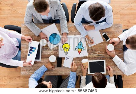business, people, planning and team work concept - close up of creative team with papers and gadgets meeting and drinking coffee in office