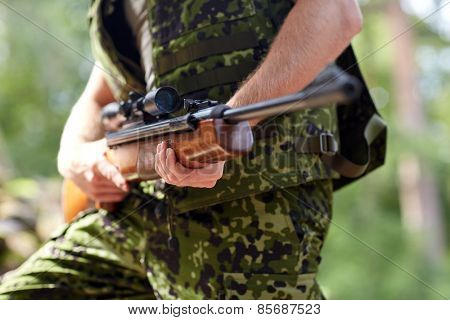 hunting, war, army and people concept - close up of young soldier, ranger or hunter hands holding gun and walking in forest