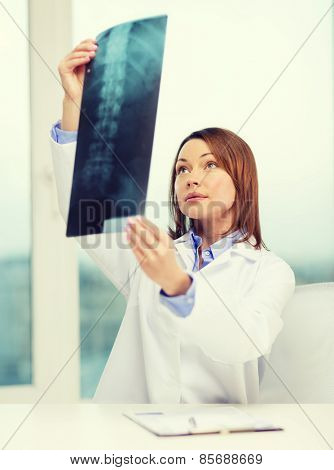 healthcare, medical and radiology concept - concentrated doctor looking at x-ray