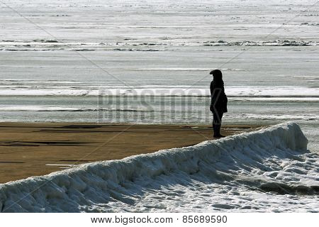 a woman waits and looks at the sea