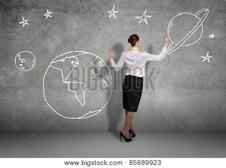 Rear view of businesswoman presenting drawn planet