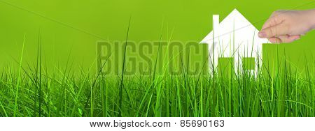 Concept or conceptual white paper house symbol held in hand by a woman in green summer grass background banner