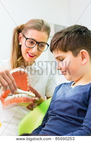 Female dentist explaining boy cleaning tooth with toothbrush on model