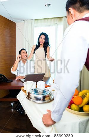 Asian room service waiter serving breakfast in hotel room