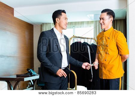 Guest giving tip to a bell boy in hotel room