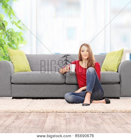 Woman drinking coffee seated by a sofa at home shot with tilt and shift lens