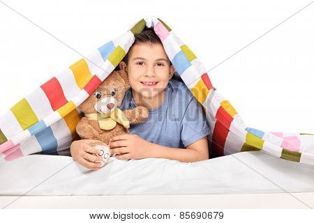 Studio shot of a playful kid holding a teddy bear under a blanket isolated on white background