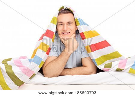 Studio shot of a carefree young man lying in a bed covered with striped multicolored blanket isolated on white background