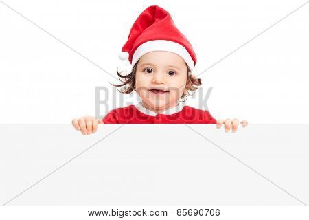 Adorable little girl with Santa hat posing behind a blank panel isolated on white background