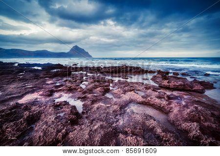 Fantastic view of the nature reserve Monte Cofano. Dramatic morning scene. Dark overcast sky. Location cape San Vito. Sicilia, Italy, Europe. Mediterranean and Tyrrhenian sea. Beauty world.