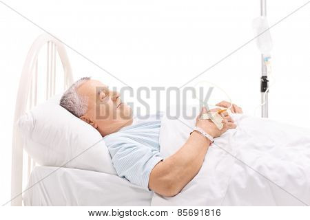 Cheerful mature patient lying in a hospital bed with an iv drip attached to his hand isolated on white background