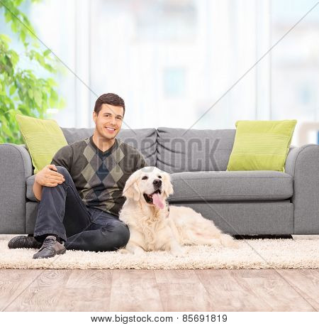 Young man sitting on the floor with his dog at home shot with tilt and shot lens