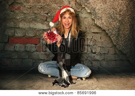 Surprised Girl In A Santa Hat Holding A Present