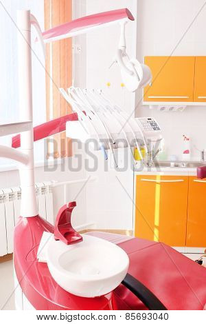 Dental clinic interior design with red chair and tools