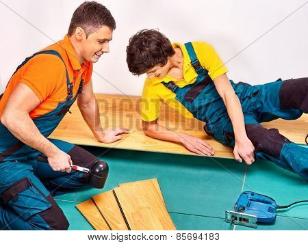 Happy men laying parquet at home.