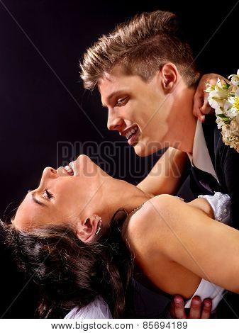 Groom kissing bride . Wedding on black background.