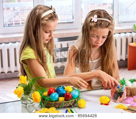 Children girl paint Easter eggs at home. Two sister.