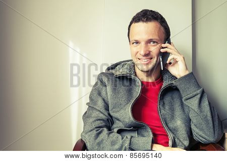Portrait Of Sitting Young Man Talking On Mobile Phone