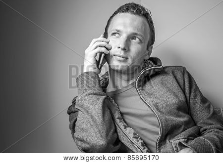 Monochrome Portrait Of Sitting Man Talking On Cell Phone