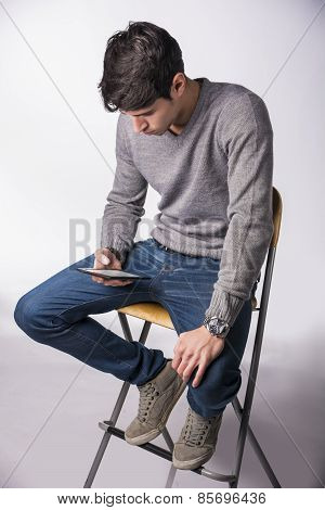Handsome Young Man Holding Ebook Reader And Reading