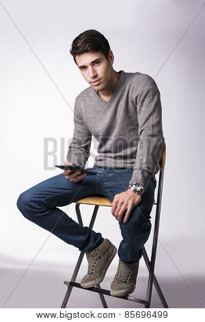 Young Man Holding Ebook Reader And Looking At Camera