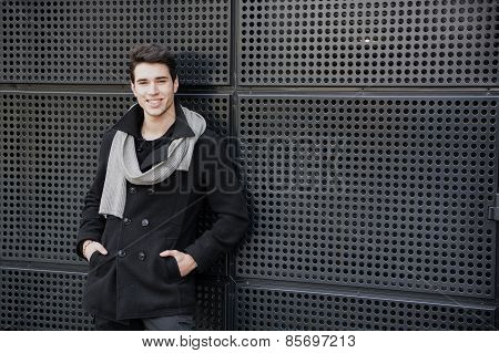 Trendy Young Man In Winter Fashion Against Wall In Urban Environment