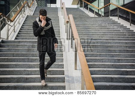Trendy Handsome Young Man In Winter Fashion Standing On A Long Staircase