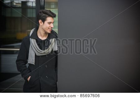 Trendy Young Man Standing Against Wall In Urban Environment