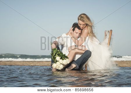 Young attractive couple sitting at water's edge on the beach