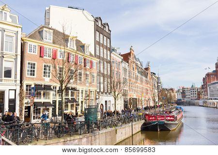 Tourists walking by a canal in Amsterdam