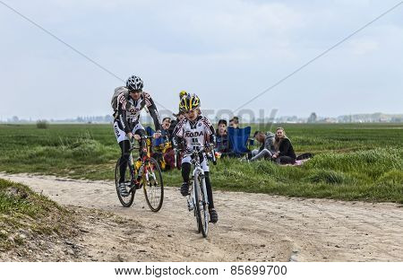 Amateur Cyclists Riding On A Cobblestoned Road