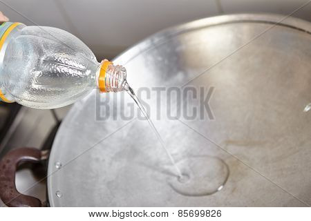 Pouring cooking oil on the wok