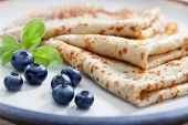 stock photo of crepes  - close up view of nice yummy crepes with blueberry on table - JPG