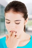 picture of vomiting  - Woman putting her finger in mouth to provoke vomiting - JPG