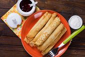 stock photo of crepes  - Pancakes or crepes on plate with raspberry jam and sour creme on wooden background - JPG