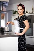 image of pinafore  - the housewife in pin up style cooking meal - JPG
